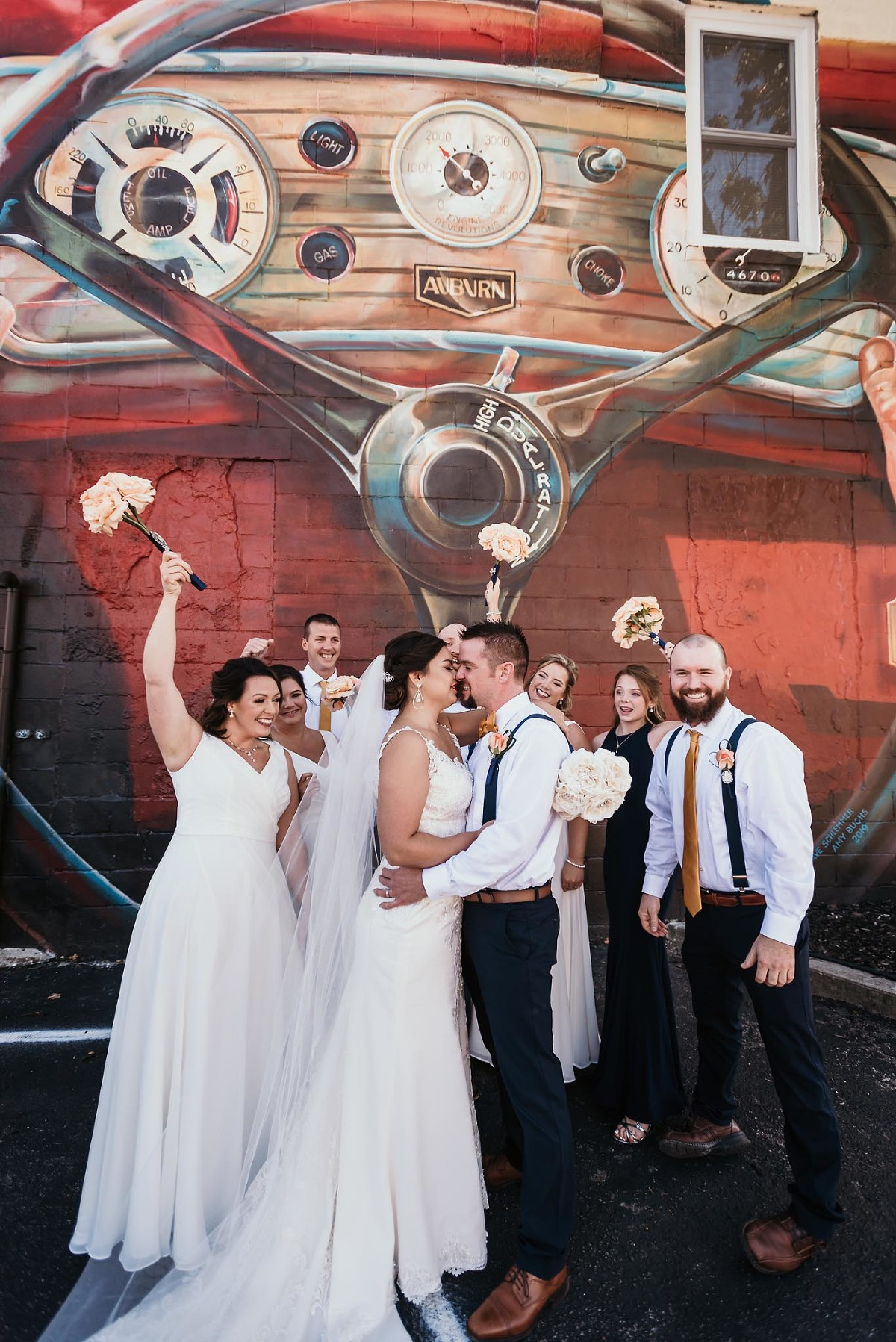 Bridal party cheering as bride and groom kiss in front of art mural in downtown Auburn, Indiana by Kasey Wallace Photography