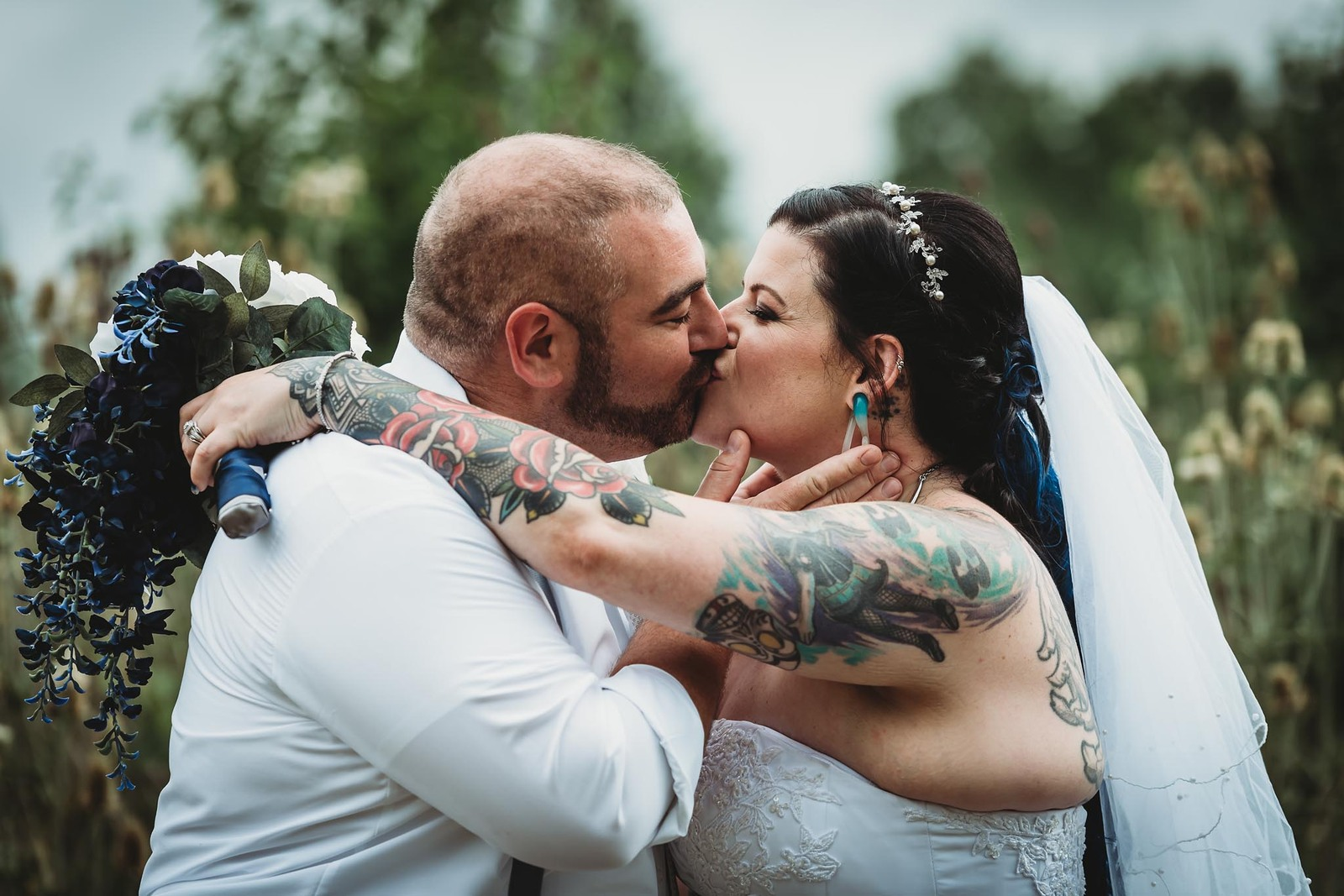 Bride with tattoos kissing groom outside at Ceruti's Catering in Fort Wayne, Indiana after summer wedding