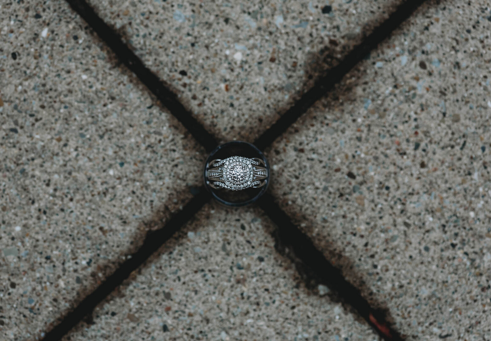 Ring details of wedding rings together on X in cement
