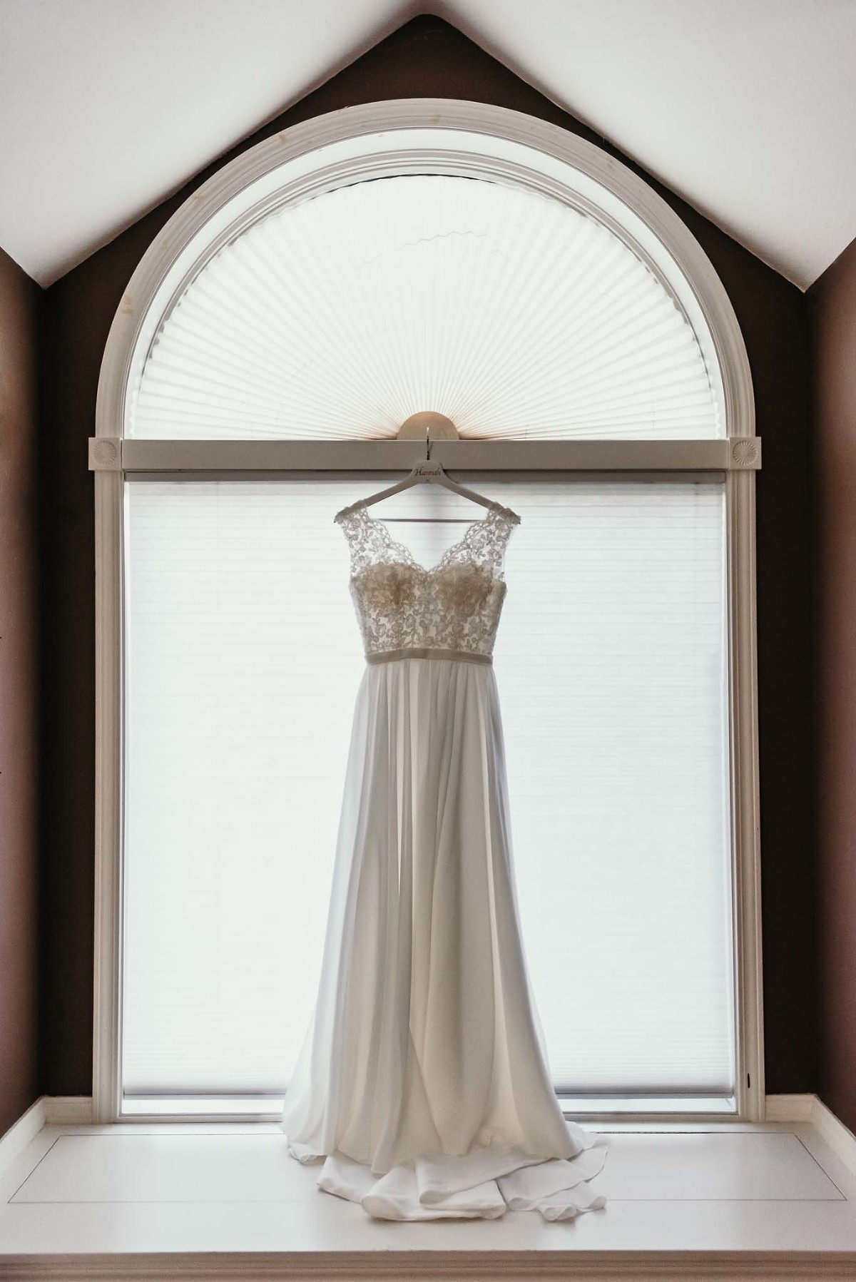 Wedding gown hanging in bride's bedroom window during fall wedding in Fort Wayne, Indiana by Kasey Wallace Photography