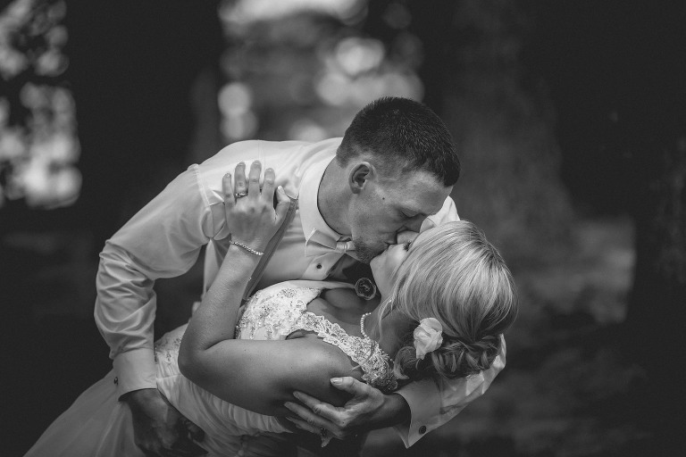 Groom dipping bride in a warm embrace, kissing outdoors, between trees after their outdoor wedding ceremony on Hamilton Lake, Indiana. Indiana wedding photography by Kasey Wallace Photography