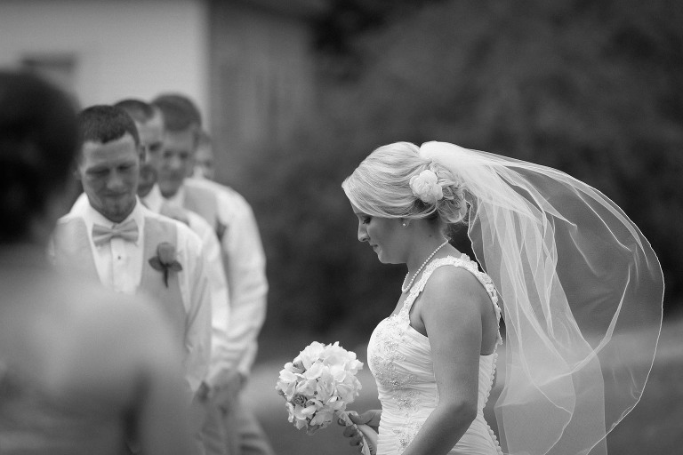 Beautiful bride walking down aisle during outdoor wedding ceremony on Hamilton Lake in Hamilton, Indiana. Bridal bouquet, wind blowing veil, flower in hair, bridal hair, bridal updo, wedding gown, black and white photograph. Indiana weddings. Kasey Wallace Photography - www.kaseywallacephoto.com
