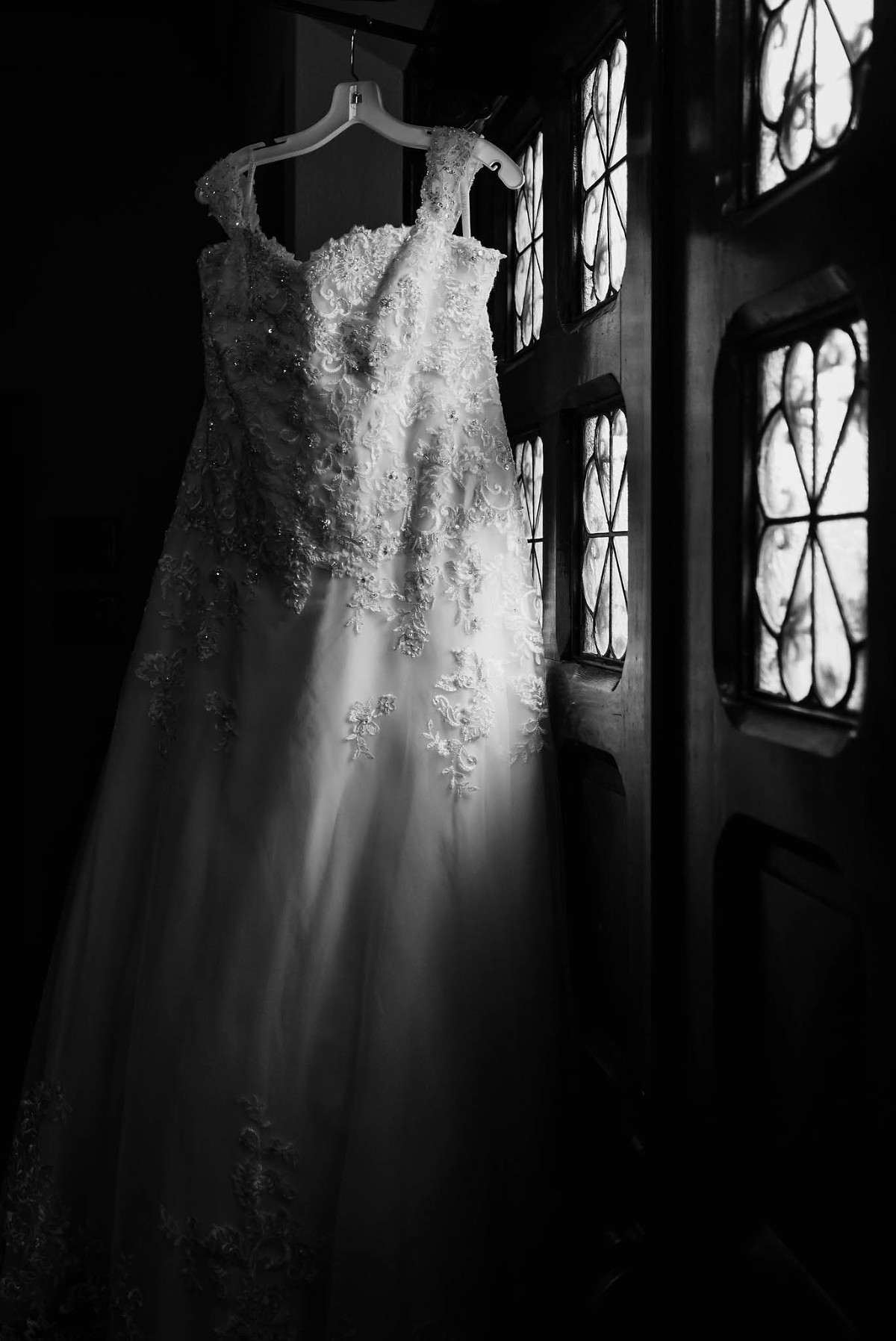 Bridal gown hanging by window light at St. Joseph Catholic Church in Garrett, Indiana, wedding photography by Kasey Wallace Photography,