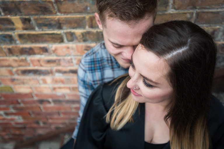Engaged couple embracing during outdoor engagement photography session in downtown Fort Wayne, Indiana by wedding photographer Kasey Wallace Photography