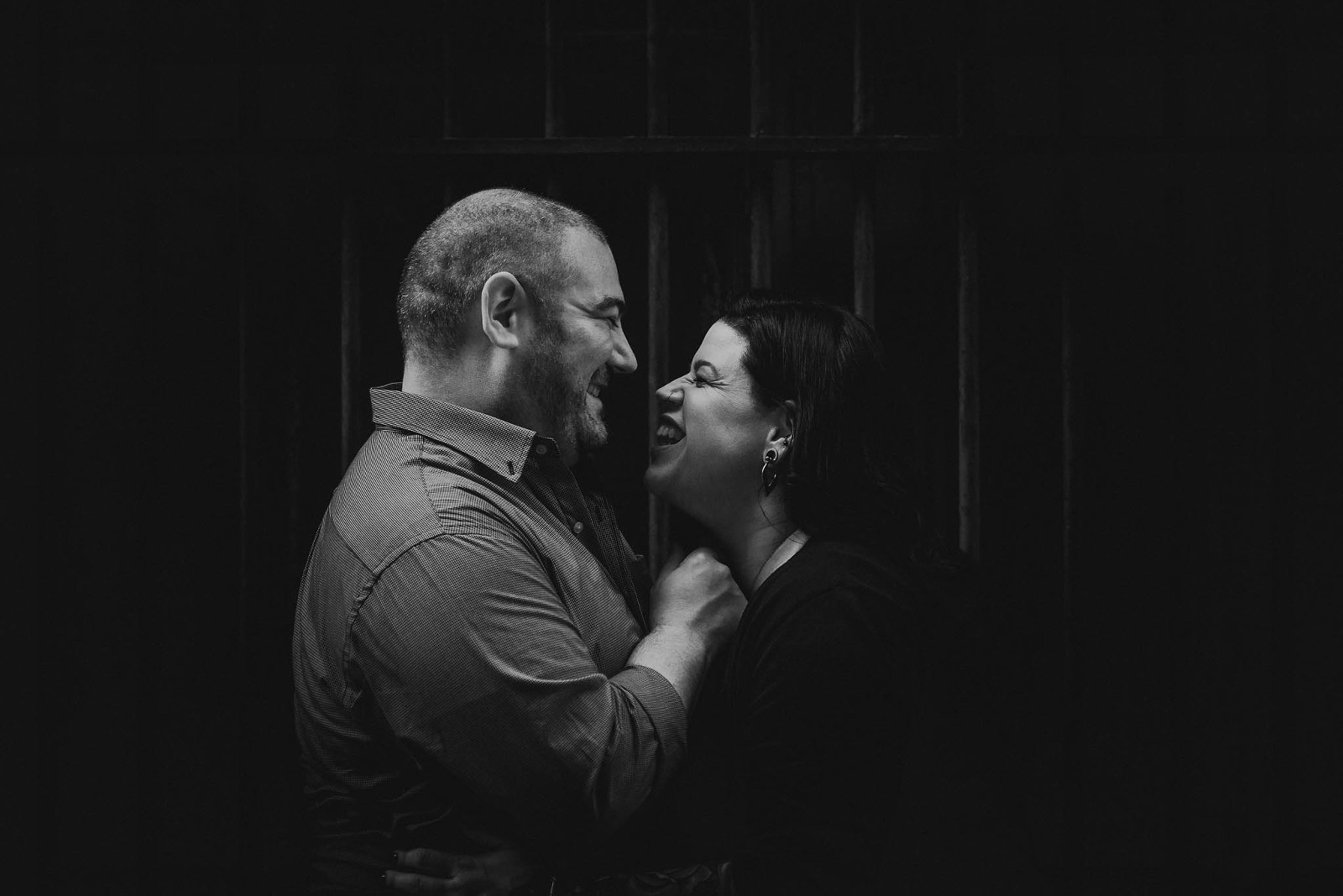 Black and white photo of guy holding girl's chin before a kiss during engagement session in Downtown Fort Wayne, Indiana