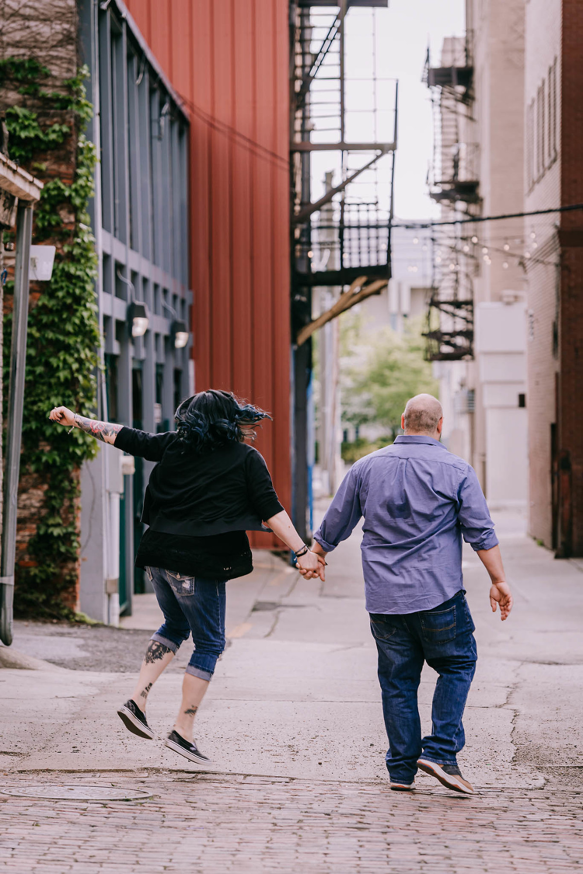 Couple holding hands and skipping in alleyway in downtown Fort Wayne, Indiana during engagement session