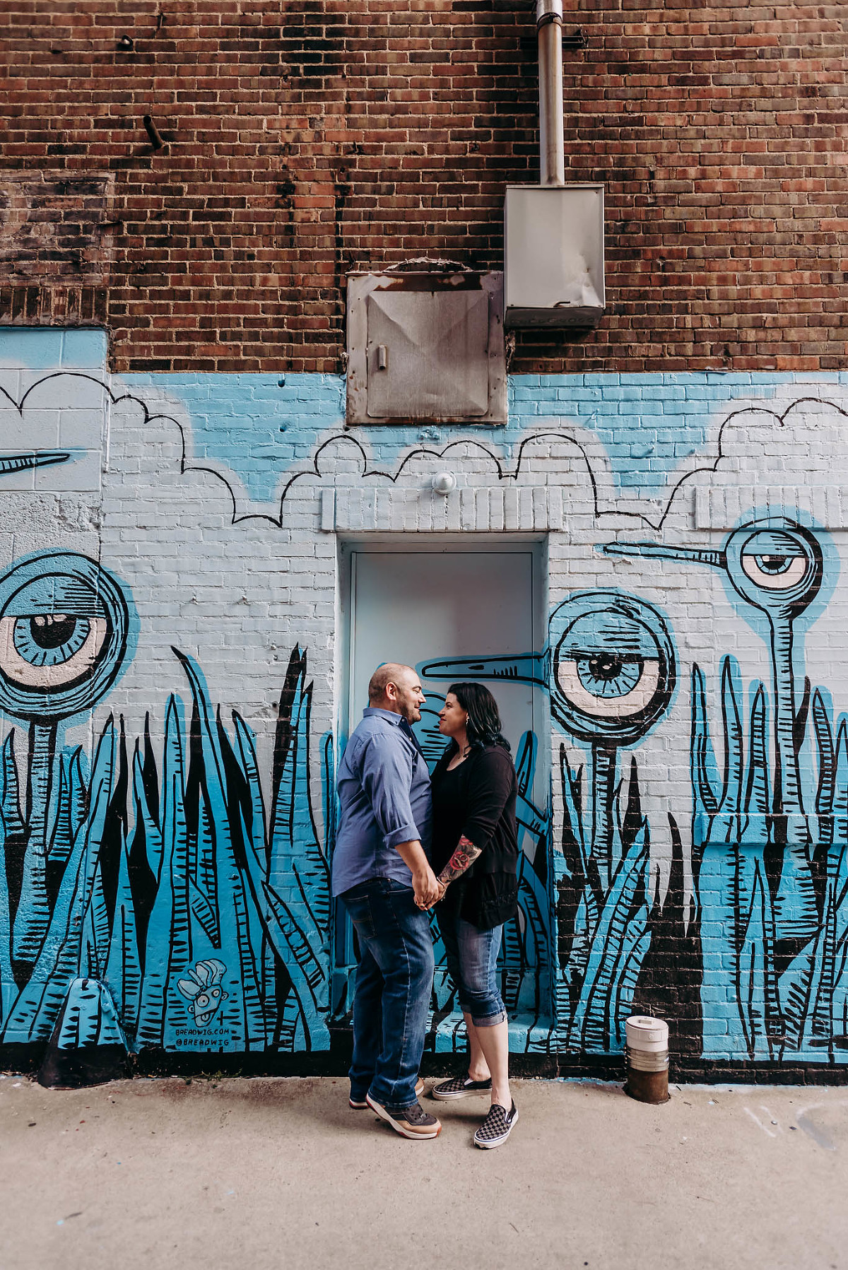 Couple gazing at each other in front of eyeball art mural by Art this Way in downtown Fort Wayne, Indiana during engagement session