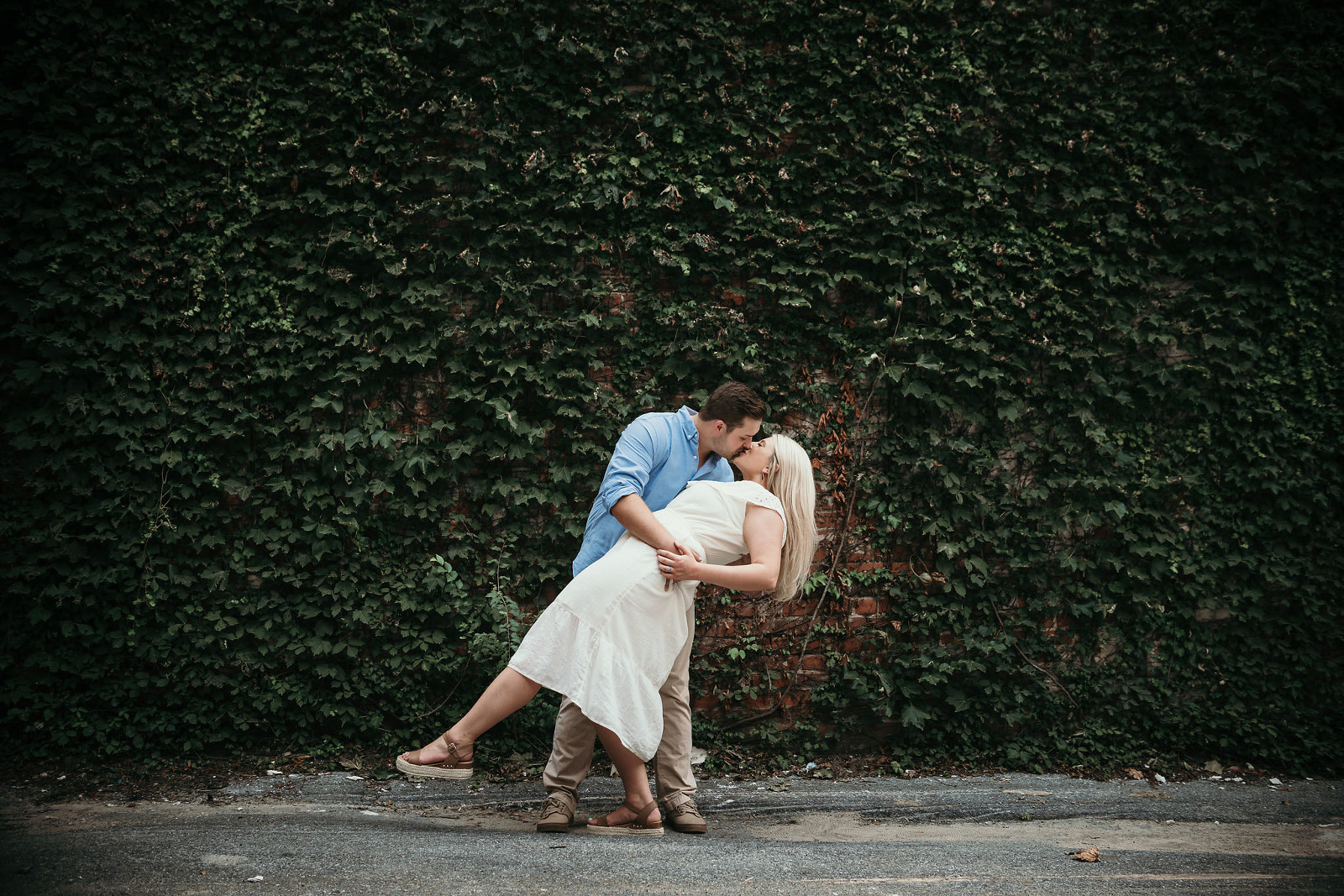 Engaged couple embracing in a dip kiss during an outdoor summer engagement session in downtown Fort Wayne by Kasey Wallace Photography
