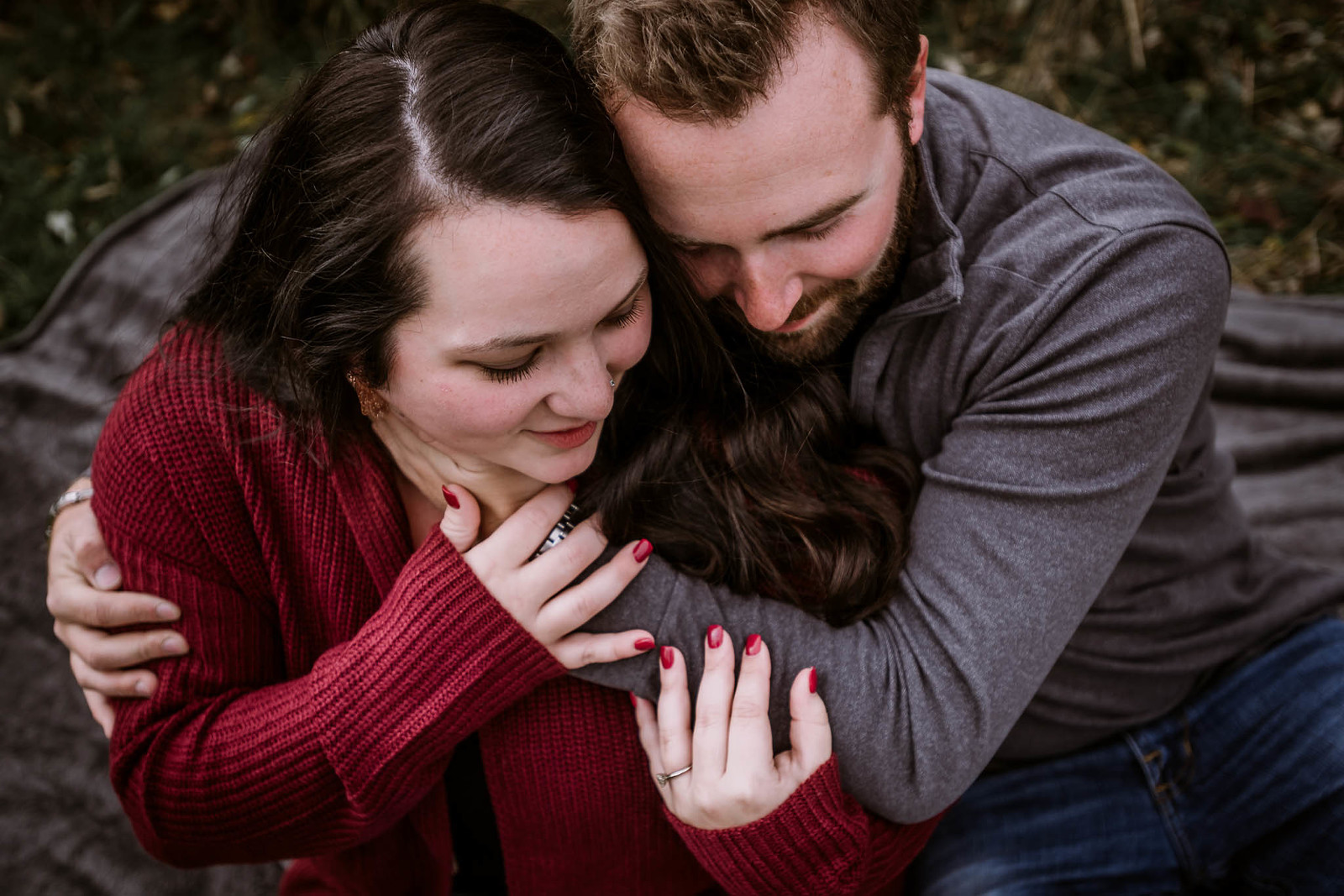 Engaged couple kissing and embracing during outdoor fall engagement session at Salomon Farm Park in Fort Wayne, Indiana by Kasey Wallace Photography