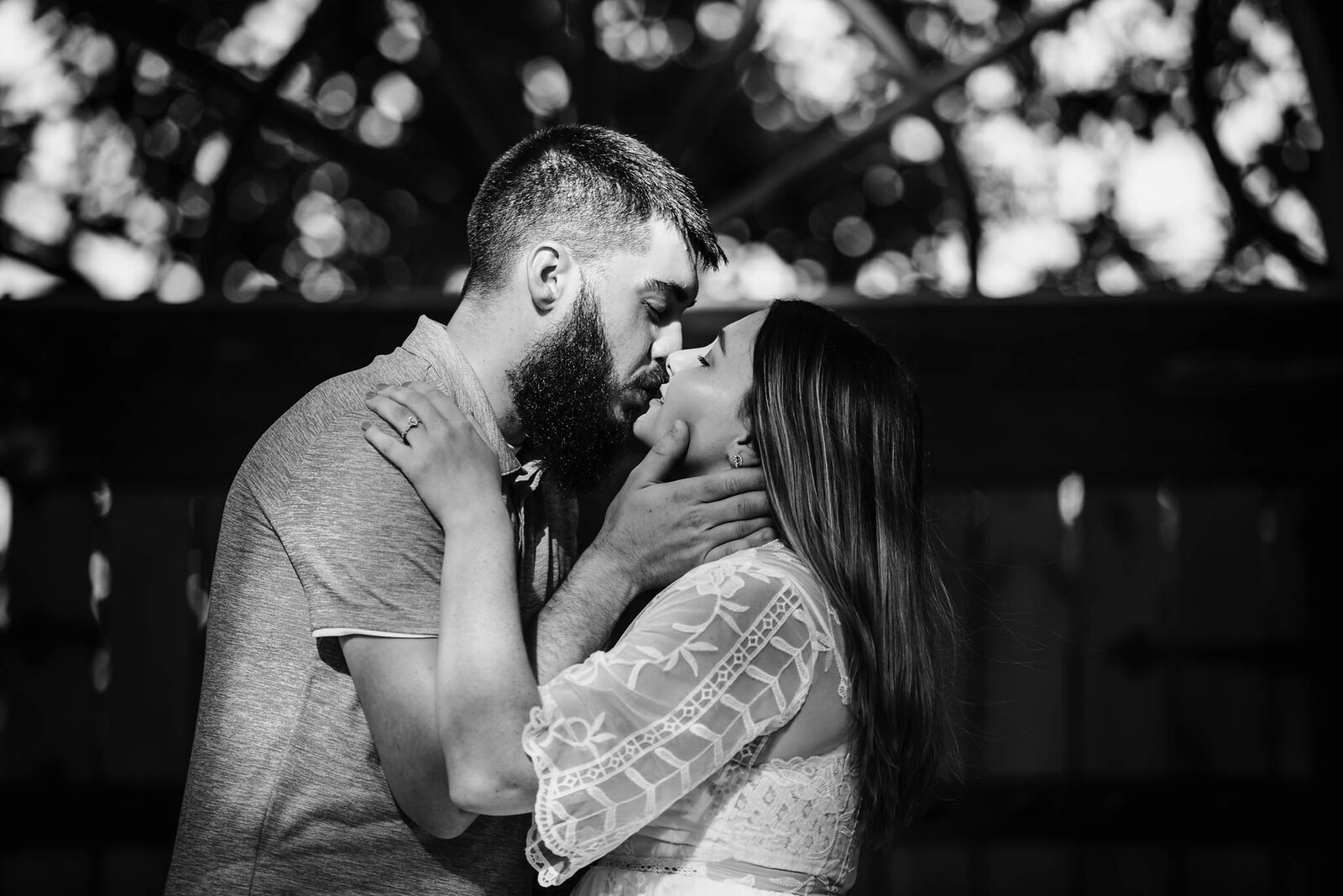 Black and white photo of engaged couple embracing and kissing
