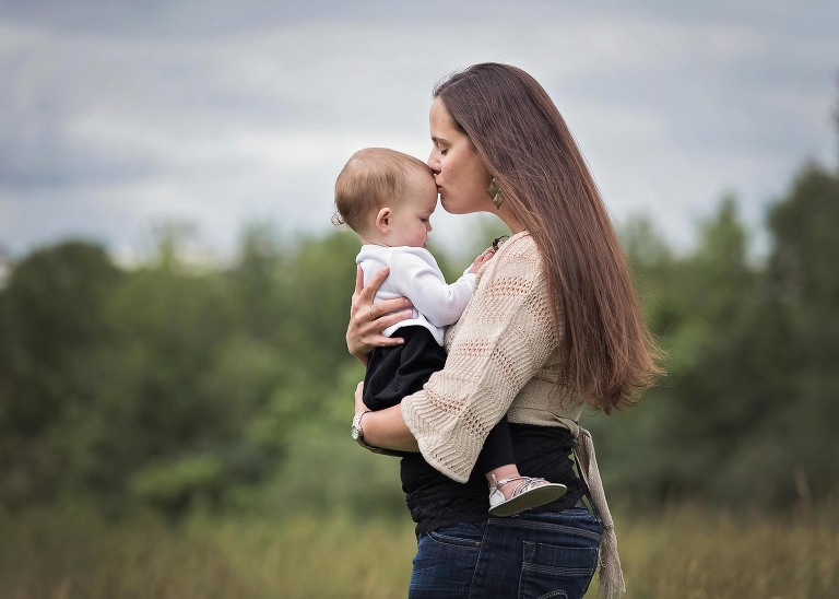 Mother holding baby daughter against her chest, kissing baby on the forehead, during an outdoor family photography session at Salomon Farm Park in Fort Wayne, Indiana, Fort Wayne family photography, Kasey Wallace Photography