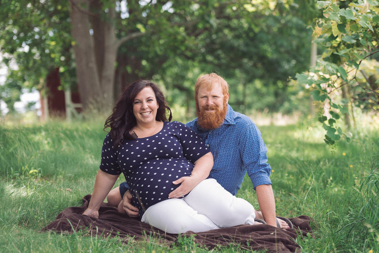 Expecting Mother Holding Baby Bump Sitting On Blanket In Field Near Fence With Husband