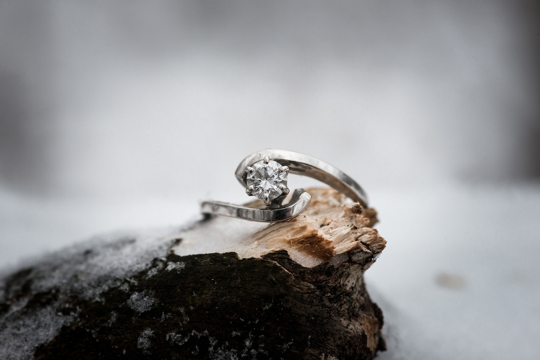 Diamond engagement ring in snow during winter engagement session in Auburn, Indiana by Kasey Wallace Photography