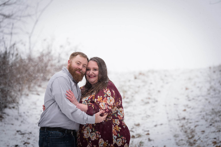 Couple embracing during snowy, wintry engagement session in Auburn, Indiana by Kasey Wallace Photography
