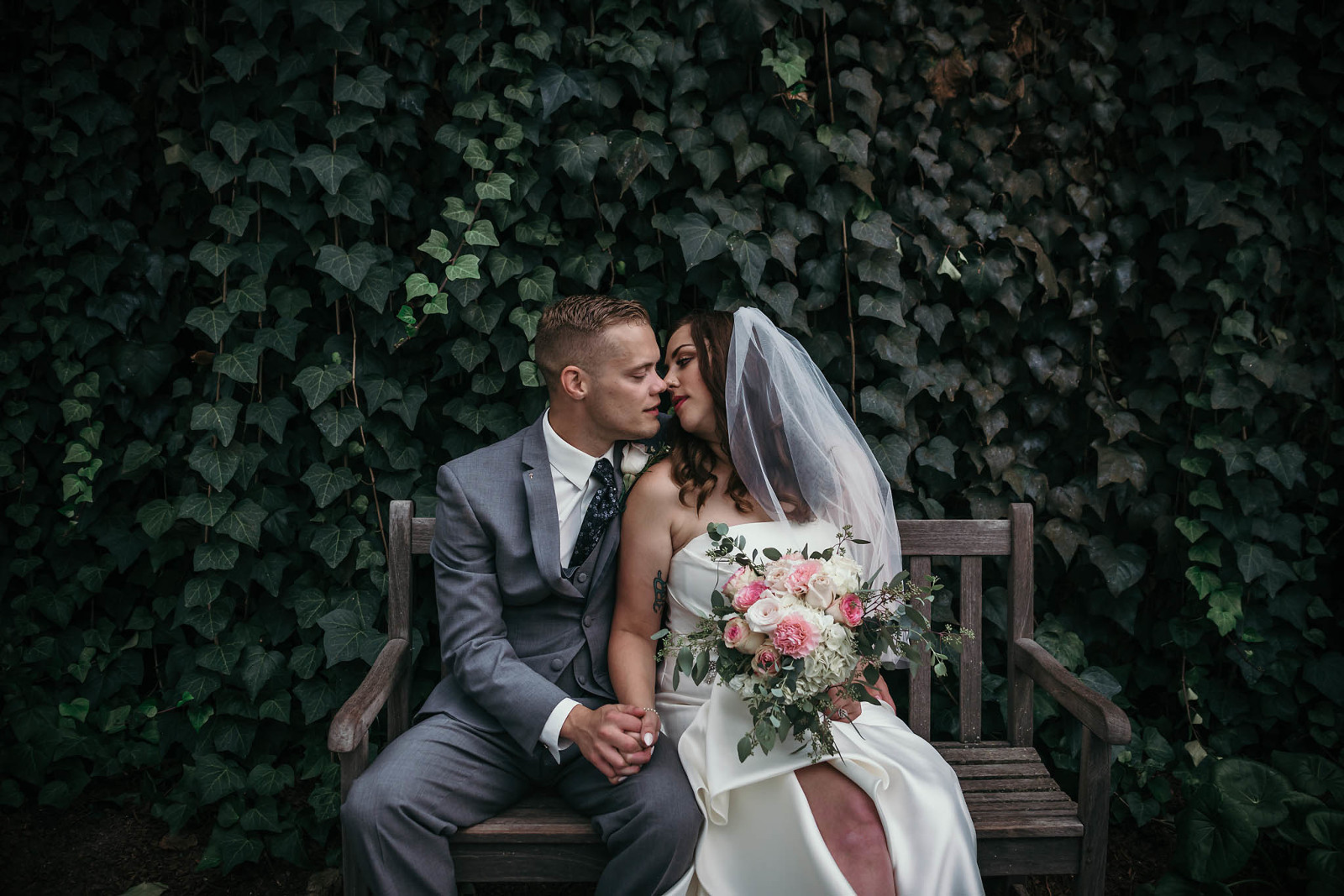 Bride and groom sitting on bench, kissing in front of ivy wall during romantic portrait session at Art Deco inspired summer wedding at the Foellinger-Freimann Botanical Conservatory in Fort Wayne, Indiana