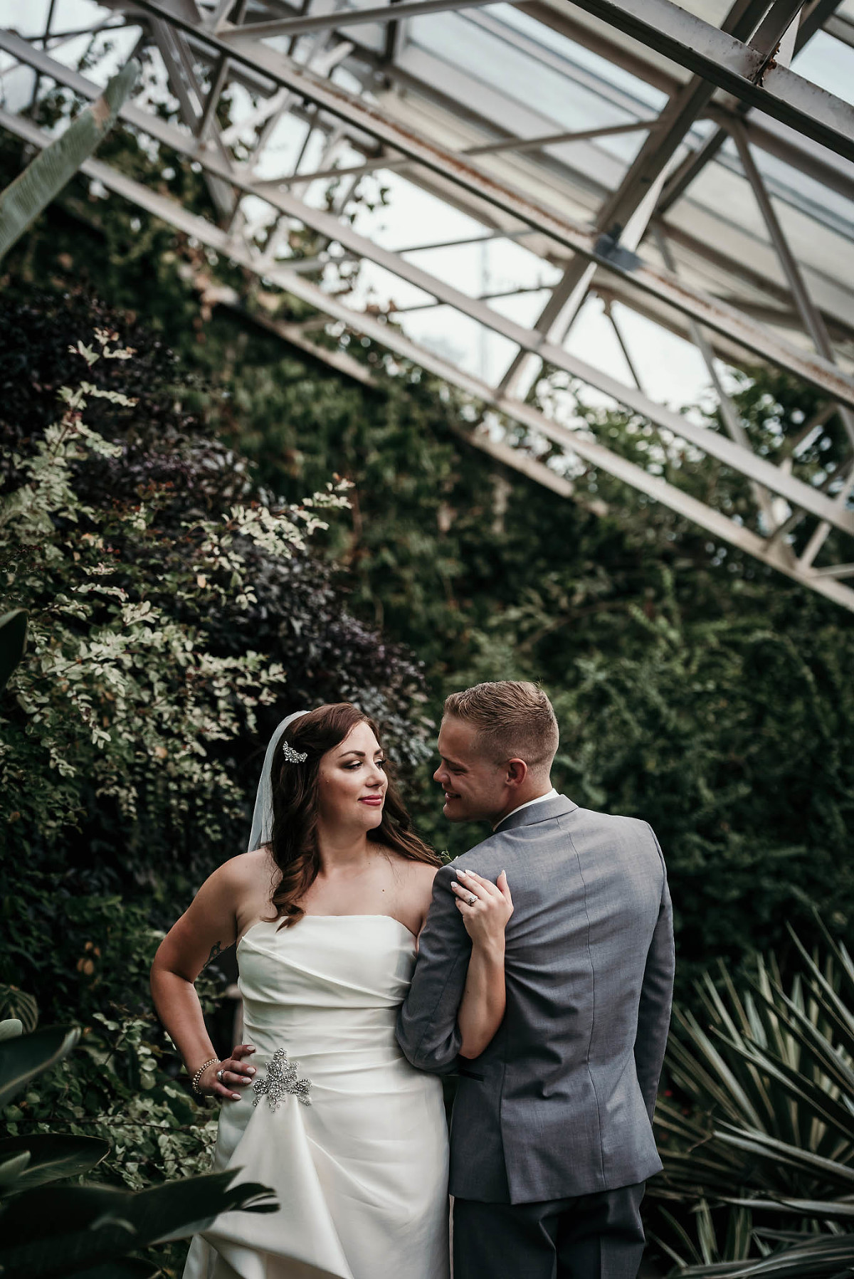 Bride and groom smiling at each other in jungle garden at Art Deco inspired summer wedding at the Foellinger-Freimann Botanical Conservatory in Fort Wayne, Indiana