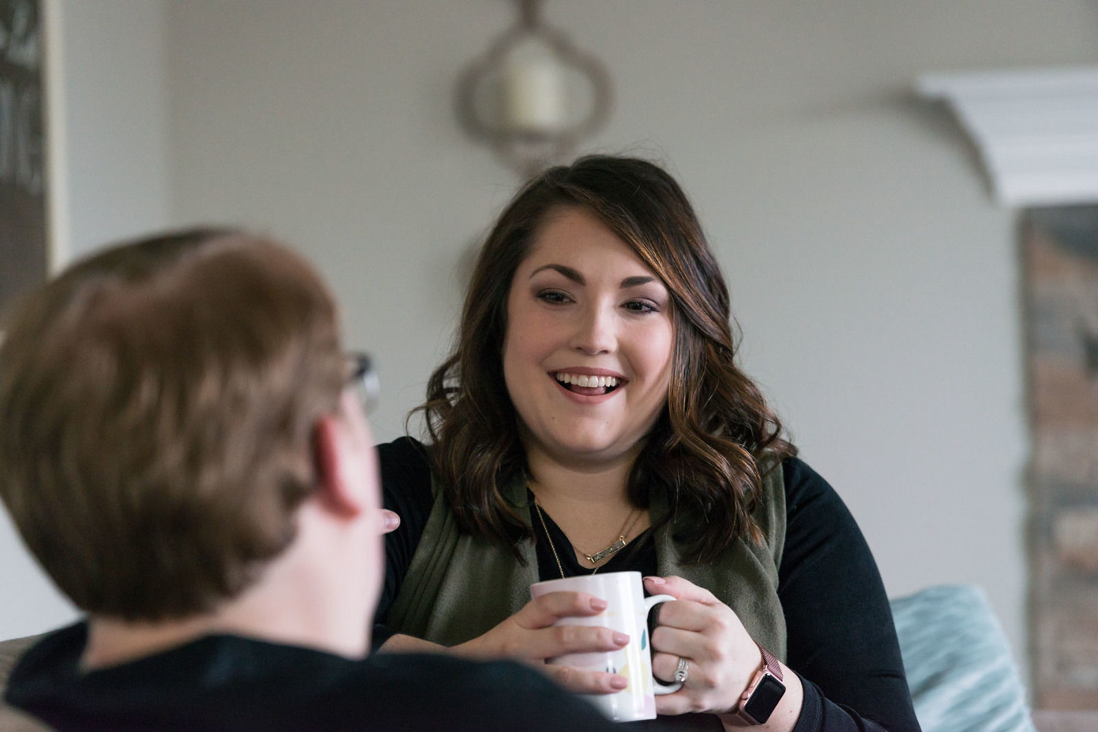 Brunette woman laughing and drinking coffee at home during personal branding session for city government campaign in Fort Wayne, Indiana