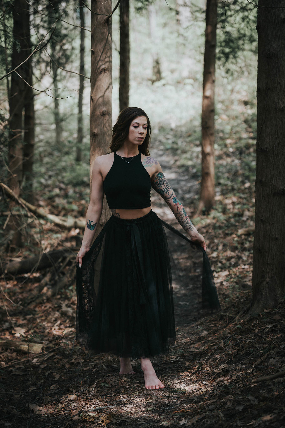 Brunette woman holding tulle skirt while modeling in nature preserve during personal branding session in Fort Wayne, Indiana