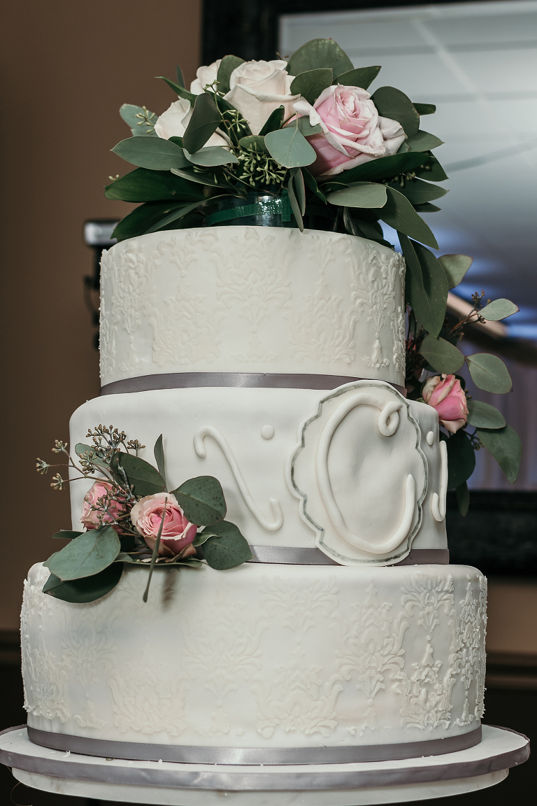 close up of three-tier wedding cake with fresh flowers at intimate country club wedding
