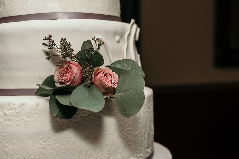 close up of fresh roses on three-tier wedding cake at intimate country club wedding