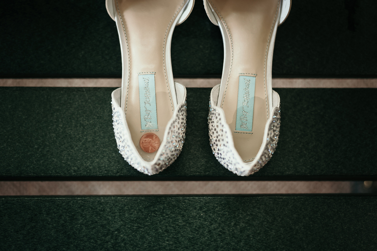 close up of a penny taped in bride's wedding shoes for good luck