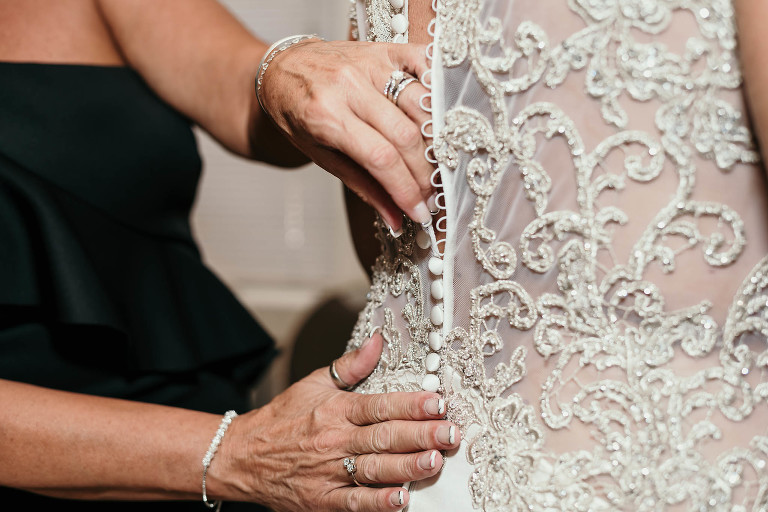 close up of mother of the bride's hands fastening the loops around buttons of wedding gown