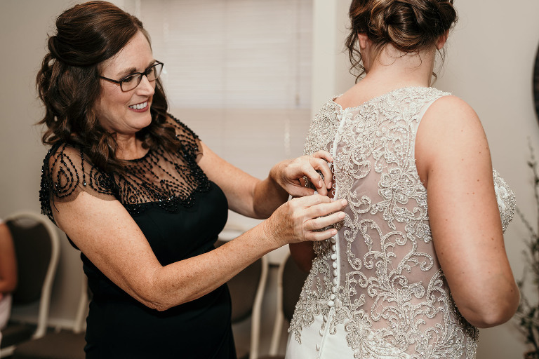 mother of the bride buttoning back of wedding dress