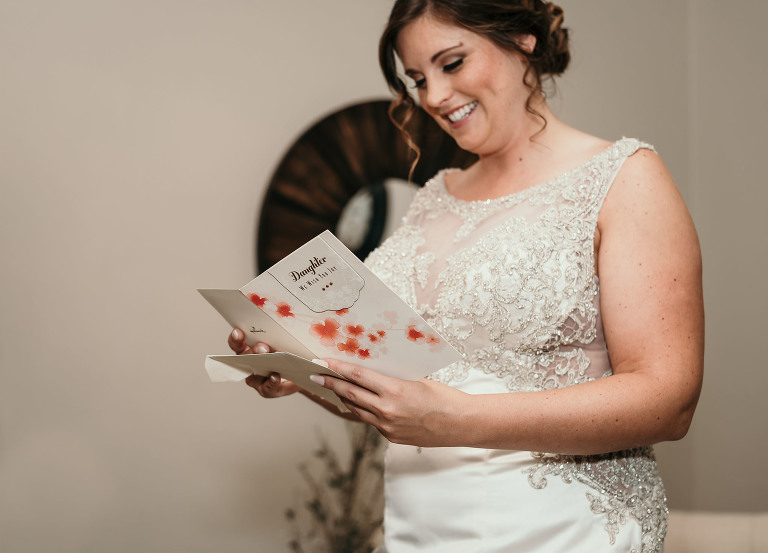 bride reading card from her mother during bridal prep