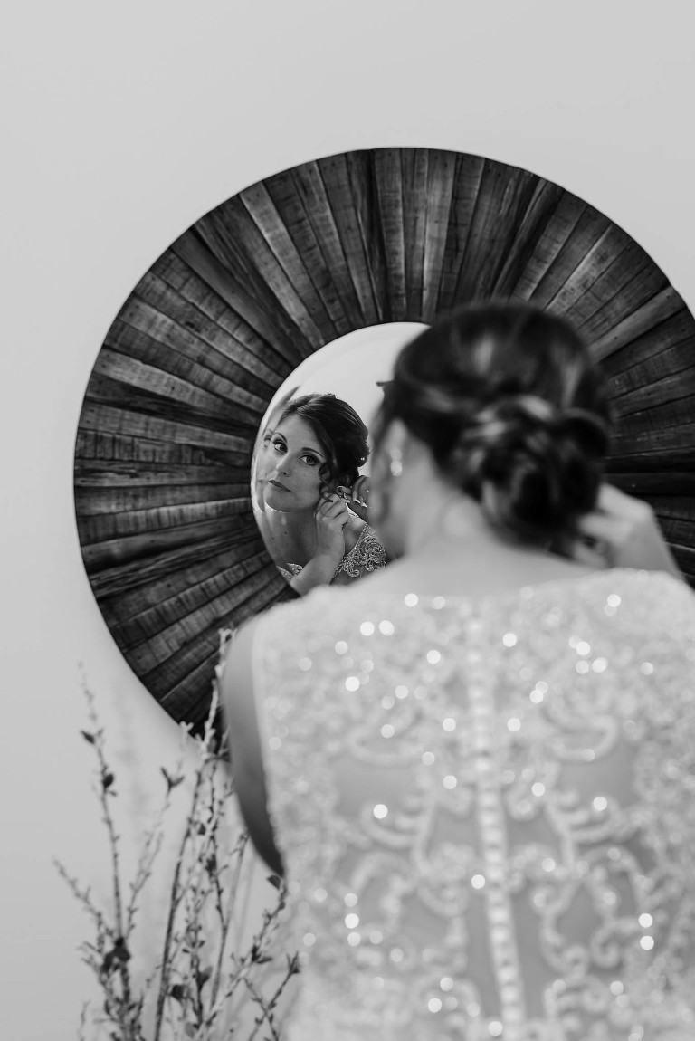 black and white photo of bride looking into circle mirror as she puts on earrings