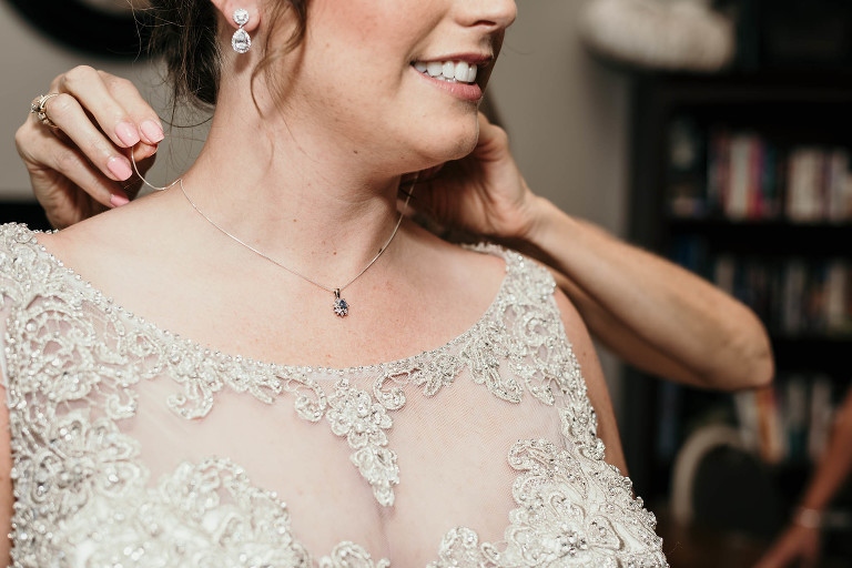 mother puts necklace around bride's neck during bridal prep before intimate country club wedding