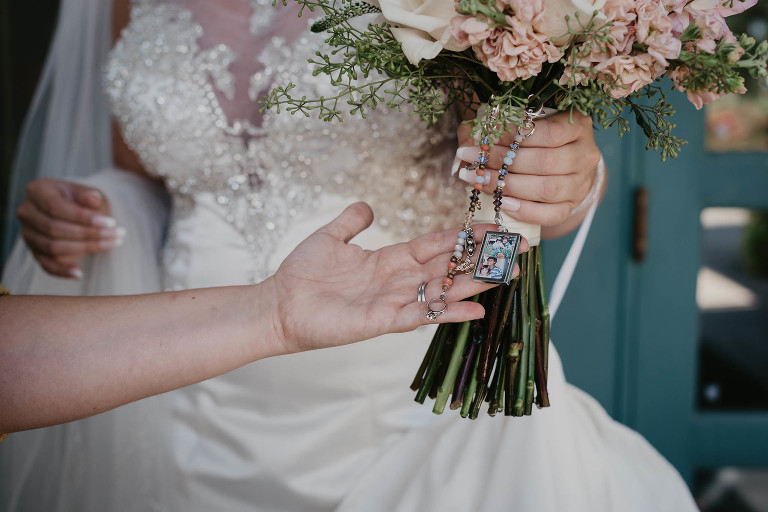 close up of picture lockets on bride's fresh flower wedding bouquet at intimate country club wedding