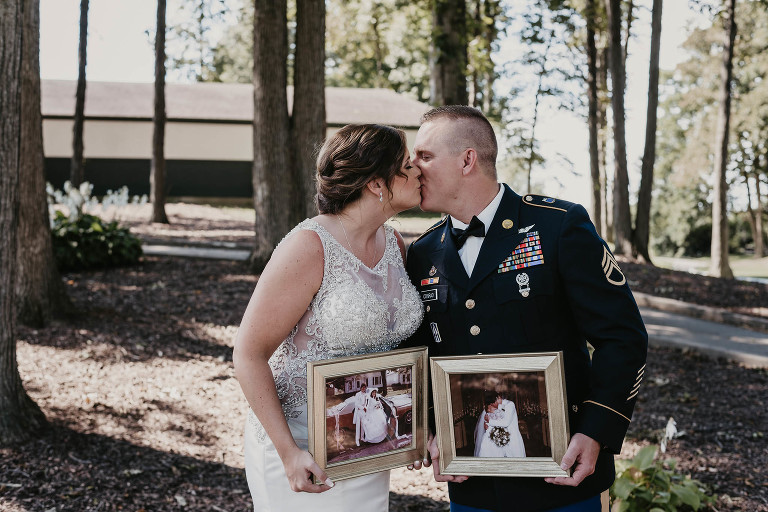 bride and groom kiss while holding photos of their parents on their wedding days