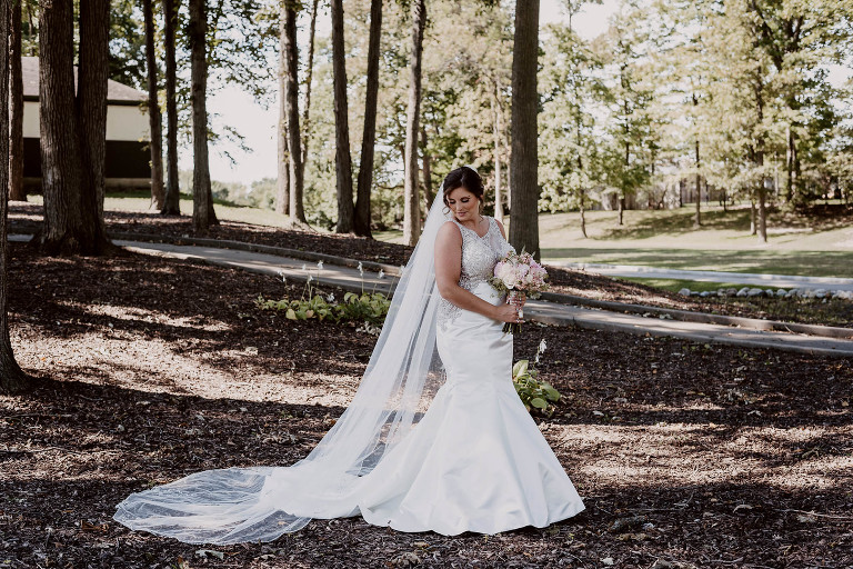 bride holding fresh flower bouquet and gazing down at her dress outside between trees at intimate country club wedding