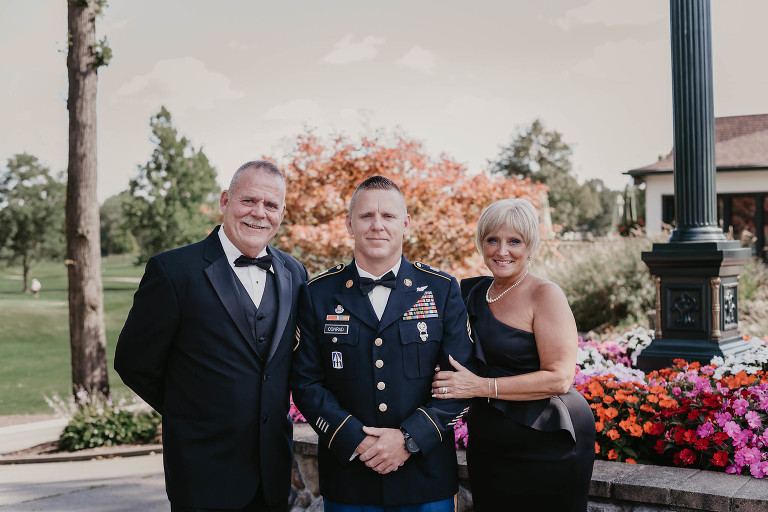 Groom standing between his parents during formal portraits outside at intimate country club wedding
