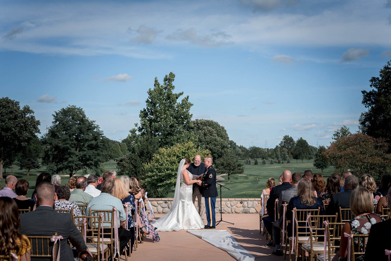 wide angle view of bride and groom standing at altar with pastor during their outdoor intimate country club wedding ceremony