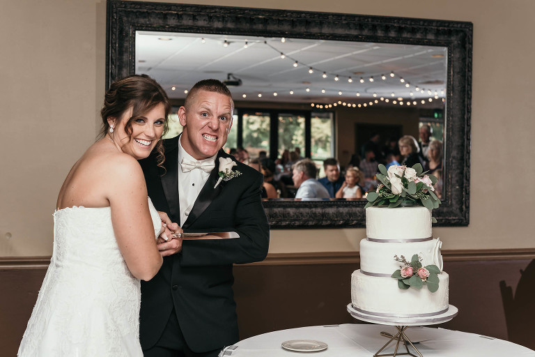 groom makes a silly face while cutting three-tier wedding cake