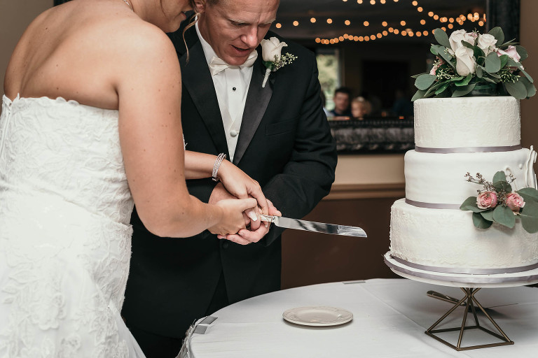 close up of bride and groom cutting their three-tiered wedding cake