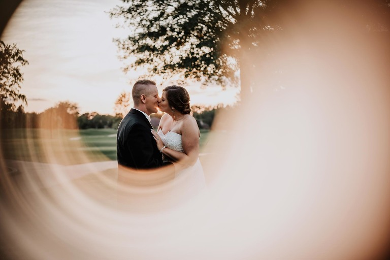 lens flare reflection of bride and groom kissing at sunset in front of pine trees on golf course at intimate country club wedding