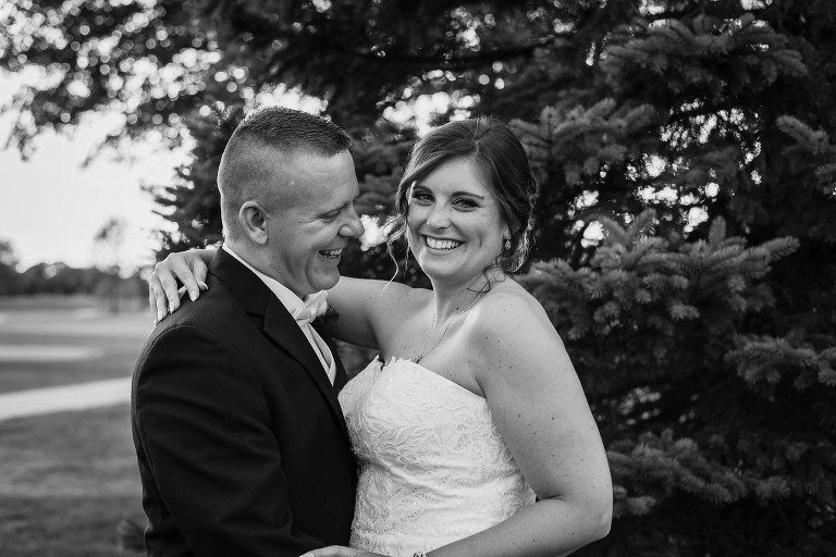 black and white photo of groom looking at bride while she smiles at sunset in front of pine trees at intimate country club wedding