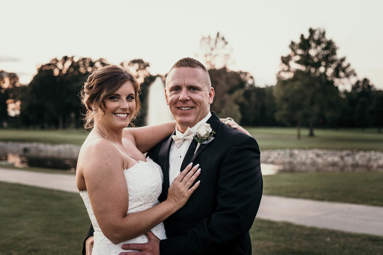 bride and groom embracing on golf course in front of fountain during sunset at Pine Valley Country Club