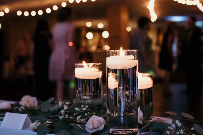 close up of lit candles in water vases at wedding reception