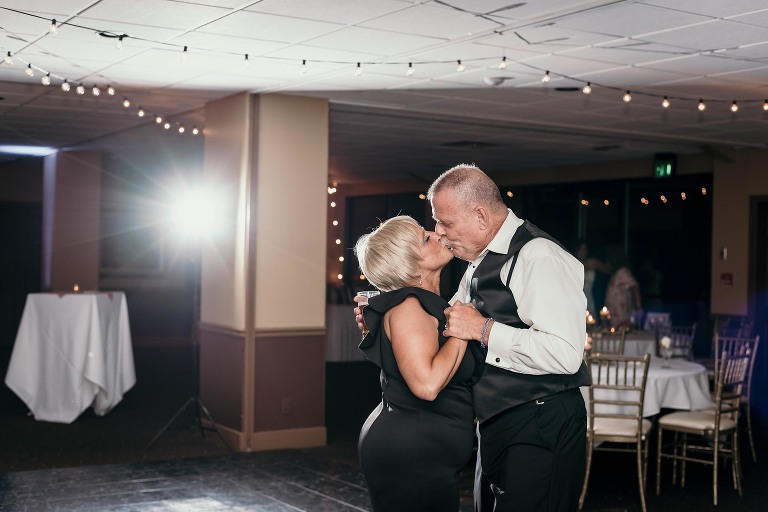 Mother and father of the groom kissing while dancing at reception
