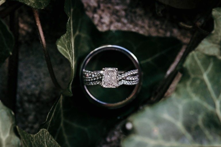close up of diamond wedding rings inside groom's ring while nestled in greenery at intimate country club wedding