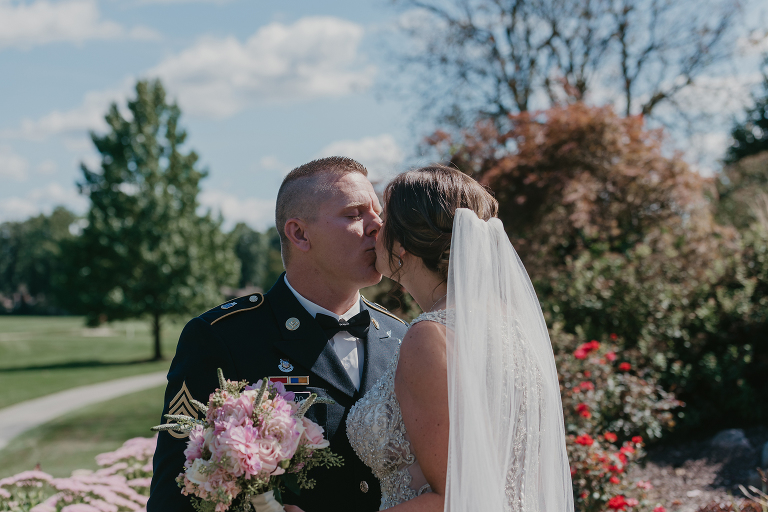bride and groom kiss during first look outside at intimate country club wedding