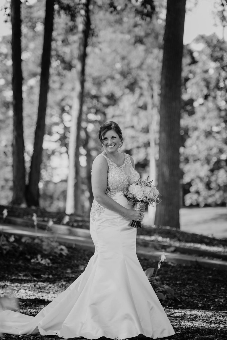 black and white photo of bride posing between trees while holding fresh flower bouquet
