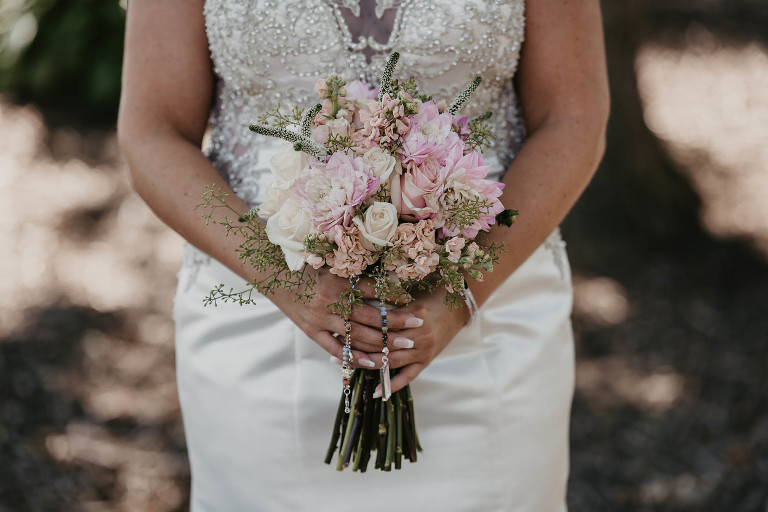 close up of bride holding her fresh flowers at waist level in front of wedding dress