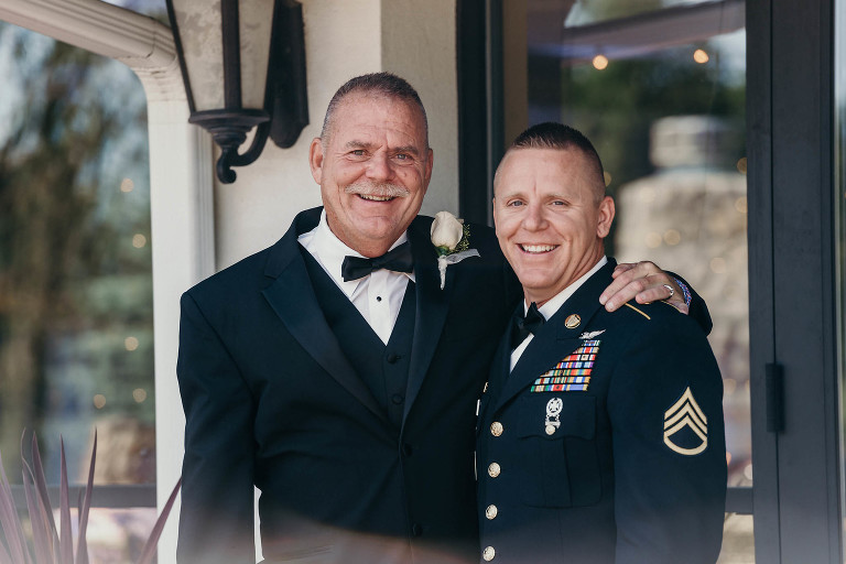 groom and father embrace and smile outside at the beginning of his intimate country club wedding