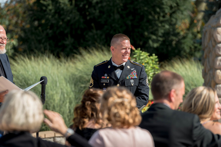 groom waits and smiles as he sees his bride approaching during outdoor intimate country club wedding ceremony