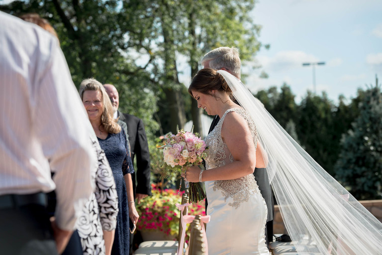 Bride walking with her father down the aisle at her outdoor intimate country club wedding