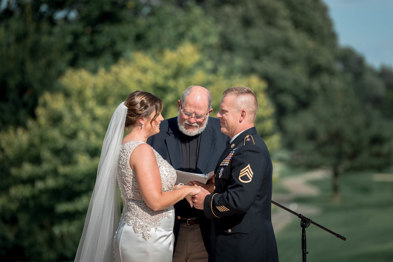 bride and groom holding hands in front of pastor during outdoor intimate country club wedding ceremony